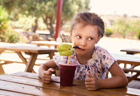 Fun cute thinking kid girl drinking smoothie juice with serious look in summer cafe. Closeup portrait