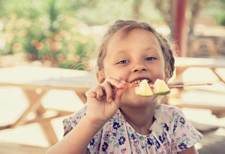 Fun cute enjoying kid girl eating the pieces of cut apples with serious beautiful big smiling eyes in summer cafe. Closeup portrait