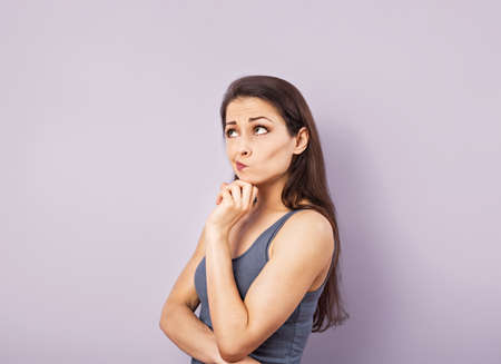 Funny grimacing brunette woman thinking and looking up in gray t-shirt with folded arms on purple background with empty copy space. Closeup portrait Stock fotó