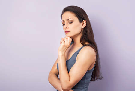 Angry grimacing brunette woman thinking and looking down in gray t-shirt with folded arms on purple background with empty copy space. Closeup portrait