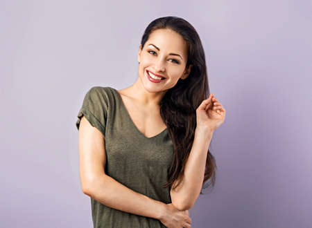 Front view of beautiful natural woman with nude makeup and toothy smile looking with folded arms in casual greet t-shirt clothing on puple background with empty copy space. Closeup Stok Fotoğraf