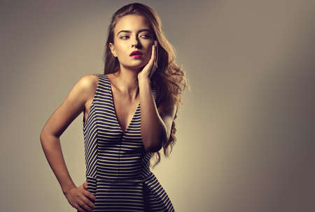 Beautiful romantic woman with long volume brown hair and pink lipstick posing in striped dress on gray background with empty copy space. Portrait fashion style. Toned bright colors