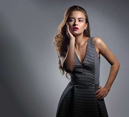 Beautiful romantic woman with long volume brown hair and pink lipstick posing in striped dress on gray background with empty copy space. Portrait fashion style