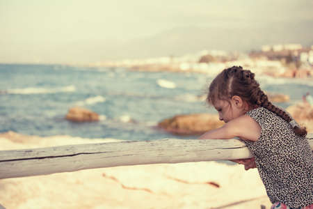 Thinking kid girl looking and joying on blue sea and vacation sky. Closeup holidays outdoors portrait with nature view background