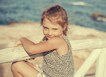 Tired from sunny weather kid girl looking unhappy and wanting to rest on blue sea background and vacation sky. Closeup holidays outdoors portrait