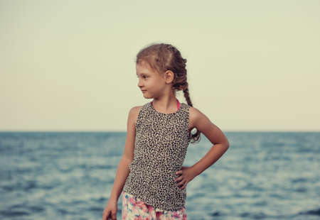 Happy kid girl posing and looking on blue sea background and vacation sky. Closeup holidays outdoors portrait