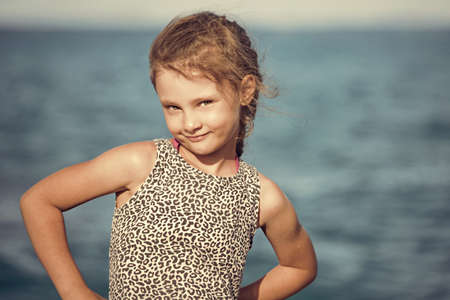 Happy smiling kid girl rposing and joying on blue sea background and vacation sky. Closeup holidays outdoors portrait Stok Fotoğraf