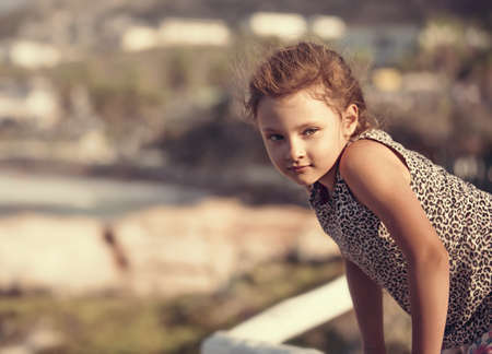 Happy kid girl relaxing and joying on vacation holidays. Closeup outdoors portrait of beautiful view of sea and city Stok Fotoğraf