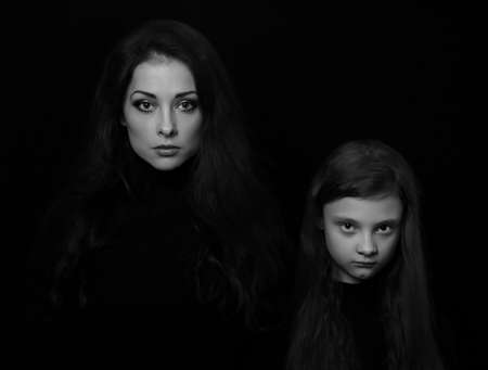 Beautiful concentrated serious mother and her angry emotional thinking daughter looking on black shadow background. Concept family conflict portrait. Black and white. Art 版權商用圖片