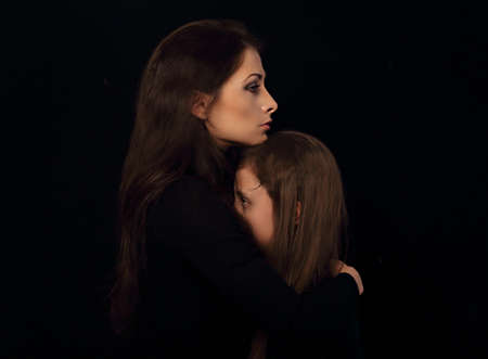 Sad serious thinking daughter hugging her unhappy mother with pensive face on black background in dark shadow. Closeup family emotional portrait with empty copy space