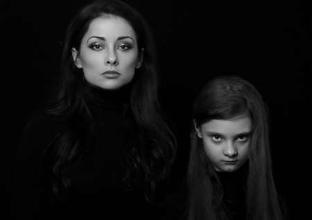 Beautiful concentrated serious mother and her angry emotional thinking daughter looking on black shadow background. Concept family conflict portrait. Art. Black and white