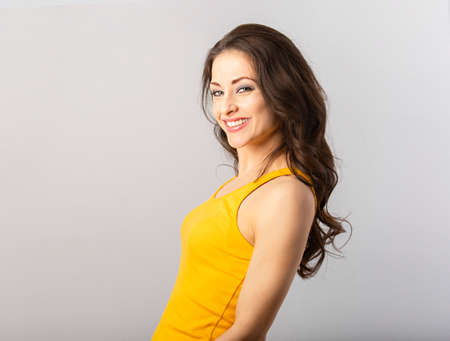 Beautiful happy toothy smiling woman with brown hair in casual yellow t-shirt looking happy on gray background with empty copy space. Closeup 写真素材