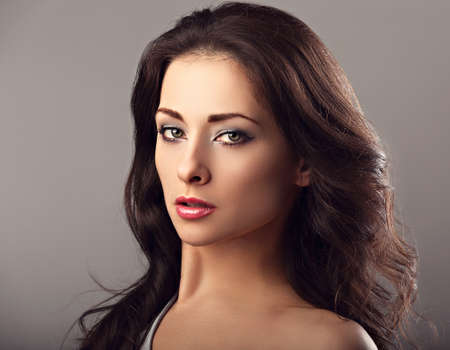 Beautiful mysterious woman makeup face and healthy volume brown hair with wisdom emotional look on brown color background with empty copy space. Closeup portrait. Stockfoto