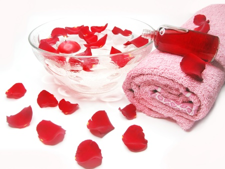 spa bowl with pink water with rose petals and cremes photo