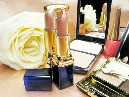 brown lipstick powder yellow rose eye shadow and pefume on satin cloth background photo