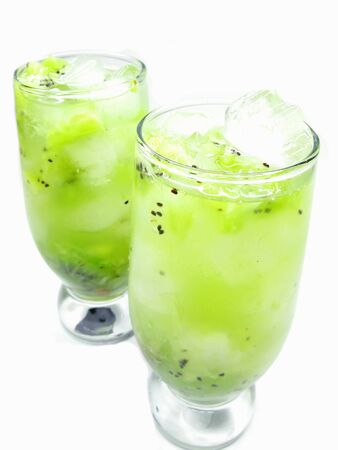 two glasses of fruit green kiwi juice drinks with ice and mint photo