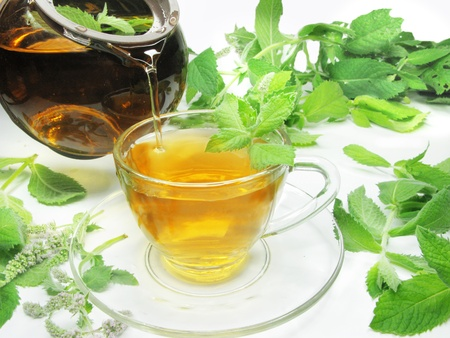 pouring mint tea into cup among leaves photo