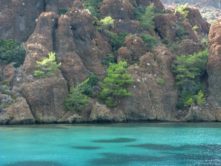 woody bay: aegean sea landscape view of red mountains and cliffs Stock Photo