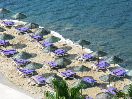 aegean sea landscape view of beach sun-tents and sun-beds photo