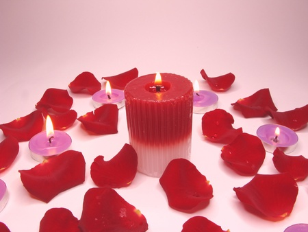 spa lit candles among damask rose petals photo