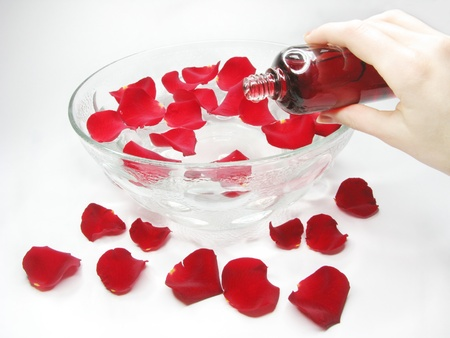 hand in plate with clean water for spa with rose petals photo