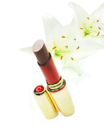 red lipstick in gold box with white lilies on background photo