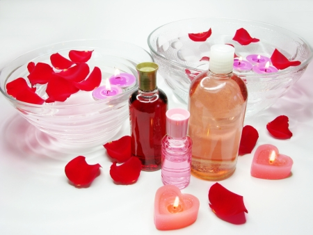 essences: spa bowl with pink water with rose petals and oil essences Stock Photo