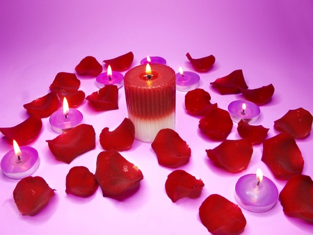 spa lit candles among damask rose petals photo