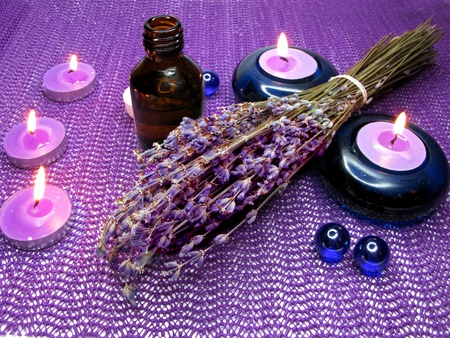 spa lit candles among lavender and bottles photo
