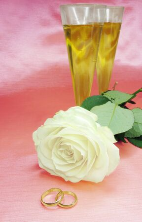 white rose and wedding rings on satin pink background photo