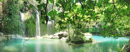 waterfall in deep forest falling view out of grotto panorama Stock Photo