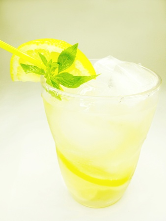 glass of fruit yellow lemonade with ice and mint photo