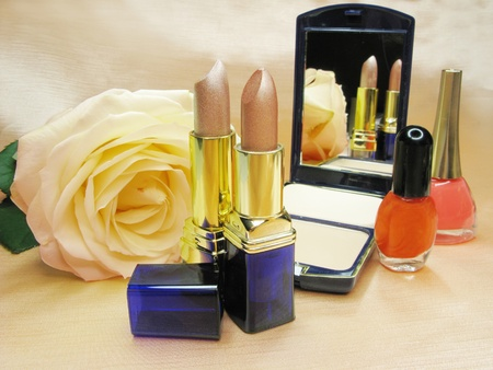 two brown lipsticks powder yellow rose eye-shadow and nail polishers  photo