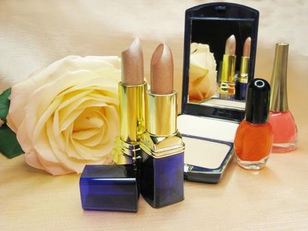 two brown lipsticks powder yellow rose eye-shadow and nail polishers
