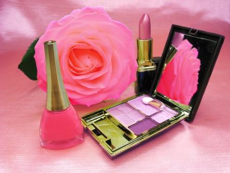 pink lipstick violet eye shadows and nail polishe on satin cloth background photo