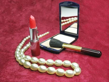 red lipstick powder white beads on purple cloth background photo