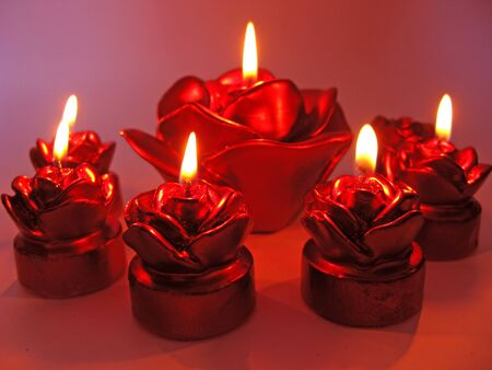 set of red rose spa aroma scented candles on dark background photo