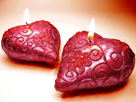 set of heart scented aroma candles on dark background photo