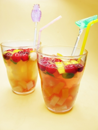 two fruit punch cocktail drinks with cherry lemon and ice photo