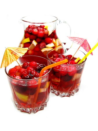 red cruchon cocktail punch in jug and glasses with ice and fruit photo