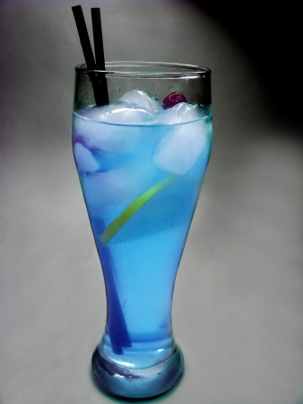 cruchon: alcoholic blue curacao cocktail with ice and lemon