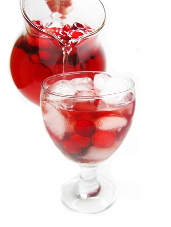 pouring fruit cruchon cocktail punch from jug into glass with ice and cherry