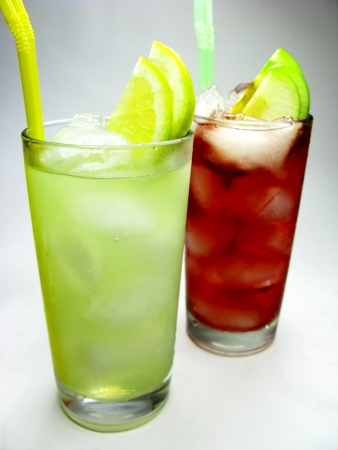 two glasses of fruit red and yellow lemonade with ice and mint photo