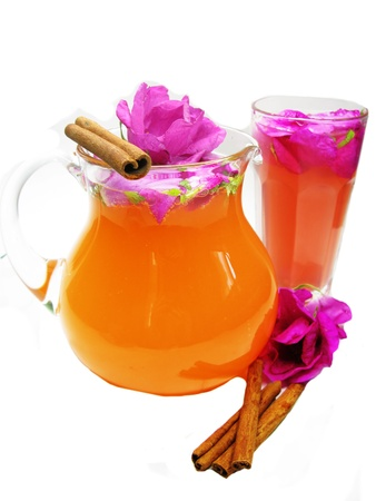 rose tea punch cocktail in jug and cup with cinnamon photo