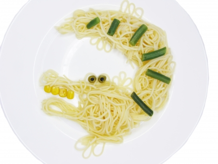 creative spaghetti food garnish with sausage crocodile shape photo