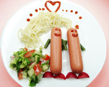 creative dinner meal with spaghetti and sausage Stock Photo