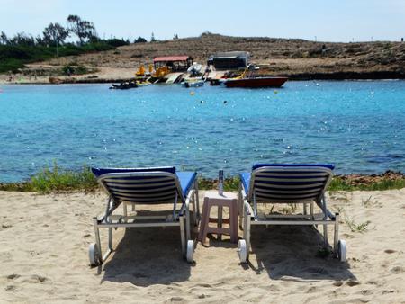 sunbeds on sandy beach coast in the mediterranean sea landscape on Cyprus island