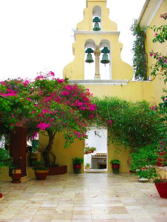 paleokastritsa: traditional monastery in Greece Corfu island with flowering bushes