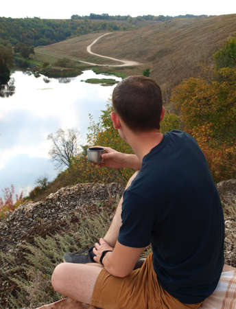 The man young sat down on the mountain and drinks tea. Looks into the distance, at the lake and the forest. Around trees and plants. Autumn season