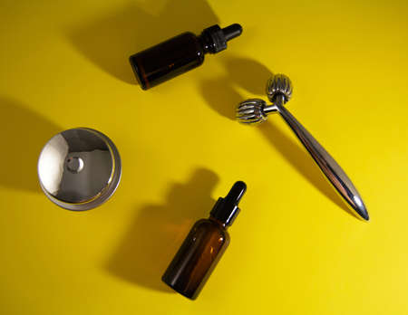 Modern selfcare concept and anti-age care. Face roller and serum on yellow background. Top view and flat lay.